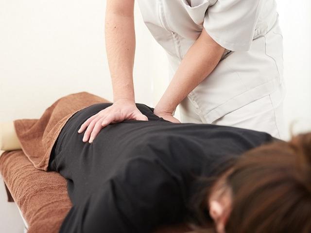 腰痛解消の指圧の施術を受ける女性